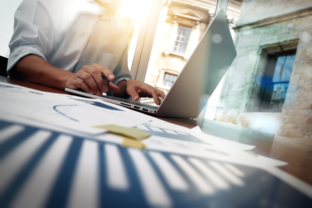 business documents on office table with smart phone and digital tablet and graph financial diagram and man working in the background-2
