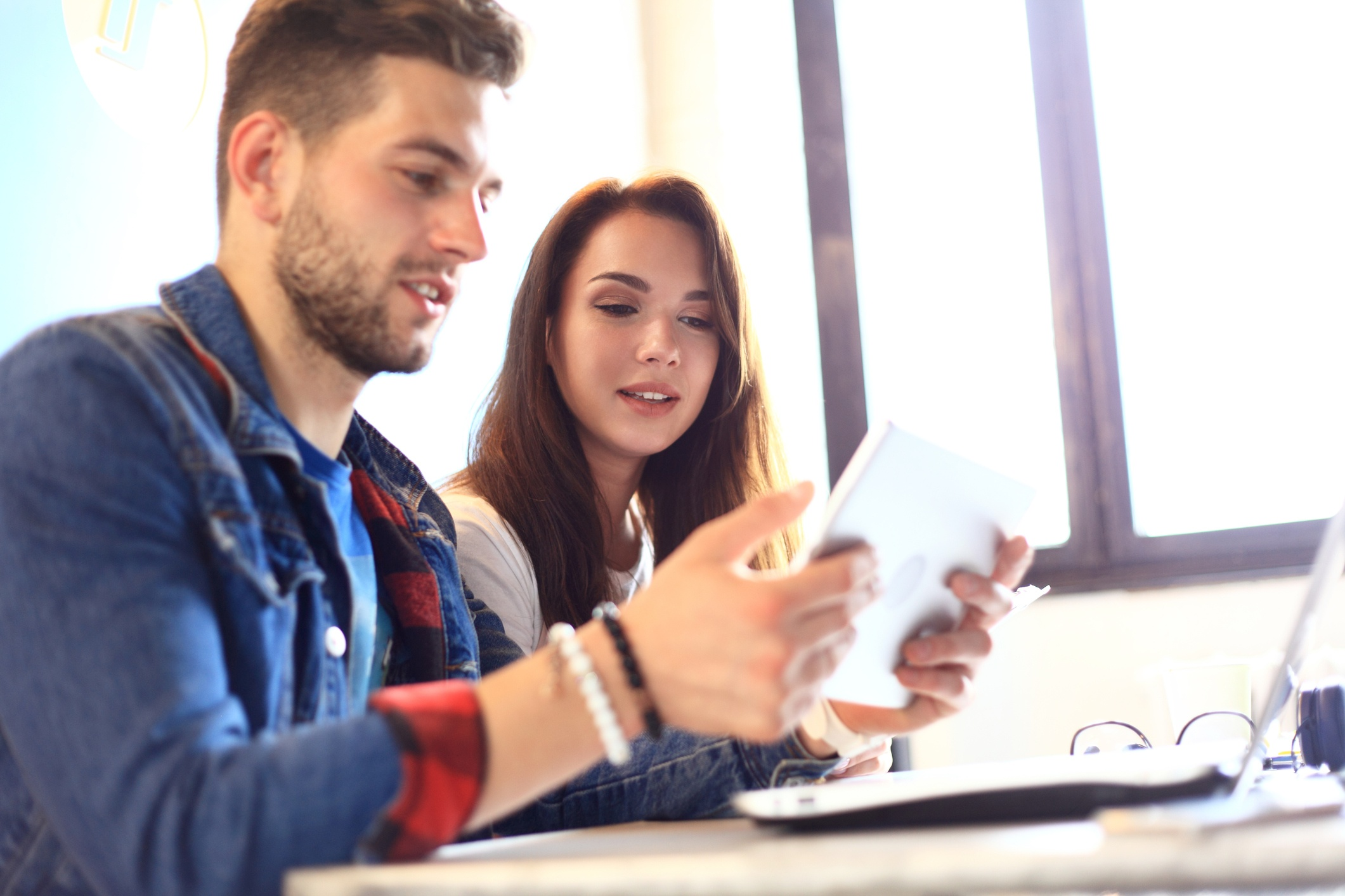 Two young employees using a tablet in the office